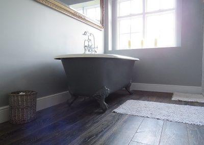 Dark Hard Wood Floor with Stylish Bath Tub with Feet